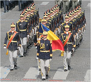 Flag of Romania - Military colors without coat of arms and weapon signs in the corners. During the march, the color bearer salutes by bowing the military colors at 45 degrees, regardless of the person. Soldiers depicted here are from the Mihai Viteazul 30th Honor Guard Regiment, participating in the 2007 Bastille Day Military Parade in Paris.