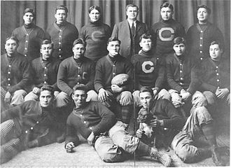 "Carlisle Indians football - The 1911 Carlisle Indians football team pose with a game ball from the upset of Harvard. Coach ""Pop"" Warner (standing, third from right) and Jim Thorpe (seated, third from right) are pictured."