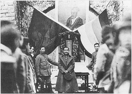 Sun Yat-sen in 1912 at one of the historic crossroads with the Five Races Under One Union flag and the Iron Blood 18-star flag 1912Jimingxiaoling2.jpg