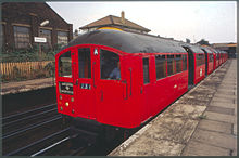 A red 1938 Bakerloo line train bound for Harrow & Wealdstone waiting at a platform at Harlesden station with its doors open