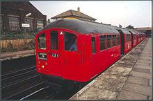 Красный поезд линии Bakerloo 1938 года, направляющийся в Harrow & Wealdstone, ждет на платформе на станции Harlesden с открытыми дверями