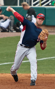 A man wearing a navy-blue baseball jersey and white baseball pants throws a baseball with his right hand
