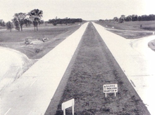 """""""A black and white photograph of a highway taken from the centre on a clear day. A small wooden sign, also in the centre, indicates that Barrie and Owen Sound are forward, while Brampton is accessed by going on the offramp to the right of the photograph. The highway disappears forward into the horizon, with trees to either side of it. There are no buildings or cars in the photo."""""""