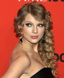 Taylor Swift stands in a Time press area. She has curled hair and is wearing a black, strapless dress.