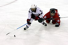 A female ice hockey player, wearing white, plays the puck as an opposing player in red falls down on the ice trying to stop her.