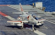 """A jet aircraft with red and white markings and the word """"Navy"""" on its tail lands on the grey deck. Smoke rises from the front tire. Water can be seen in the background."""
