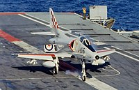 A small, single-seat jet fighter has just touched down on the flight deck of an aircraft carrier