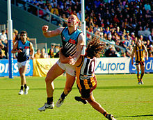 Two young male athletes contest the football. One is wearing a light blue, black and white sleeveless shirt and white shorts, while the other is wearing a brown and gold stripped sleeveless shirt and brown shorts.
