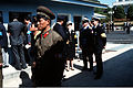 A North Korean soldier walks past reporters and members of the United Nations Command staff waiting outside the building in which the 458th Military Armistice Commission meeting is being held DN-ST-91-02137.jpg