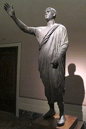 Etruscan origins - The Orator, c. 100 BC, an Etrusco-Roman bronze statue depicting Aule Metele (Latin: Aulus Metellus), an Etruscan man wearing a Roman toga while engaged in rhetoric; the statue features an inscription in the Etruscan alphabet