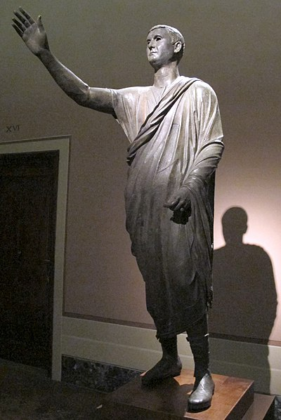 The Orator, c. 100 BC, an Etrusco-Roman bronze statue depicting Aule Metele (Latin: Aulus Metellus), an Etruscan man wearing a Roman toga while engaged in rhetoric; the statue features an inscription in the Etruscan language Arringatore 04.JPG