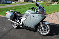 Grey motorcycle parked on an area of asphalt with red-brick paving and grass in the background