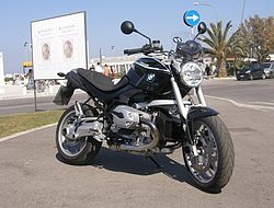 Front three-quarter view of a black R1200R parked on a street with palm trees in the background