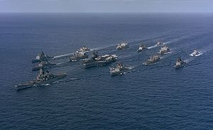 A large collection of ships sailing on the sea from the back right to the front left. At the center of the cluster of ships is an amphibious assault ship, with a battleship in front of the carrier. Other ships of various types are sailing in a roughly circular formation to provide defense for the carrier.