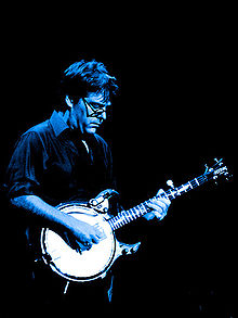 bespectacled man in shirtsleeves playing banjo