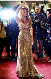 Beyoncé on the red carpet waving with photographers behind her.