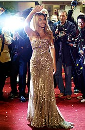 A woman waves to the crowd on a red-carpet