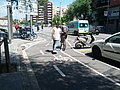 Bicyclist tows skateboarder along two-way parking-protected bikeway (17876068014).jpg