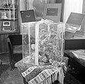 Bloemstuk verpakt een in doorzichtige doos op een tafel, op de achtergrond doxen, Bestanddeelnr 255-8529.jpg