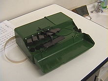 A compact green box about the size of a cigar box.  The front part of the housing forms a cover, it is folded down to the front and reveals the control elements: 6 black buttons for points 1 to 6 and in the middle a wide space bar protruding to the front.  A narrow strip of paper emerges from the housing on the left.