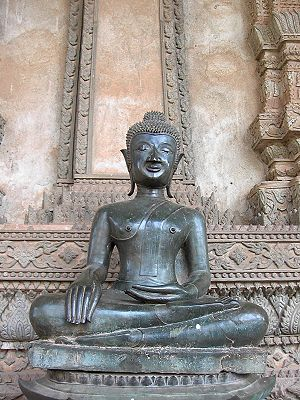 "Iconography of Gautama Buddha in Laos and Thailand - Statue of ""the Buddha calling the earth to witness,"" one of the most common depictions. The Buddha's hands are in the bhūmisparśa mudrā (Earth-touching position). Haw Phra Kaew temple, Viang Chan, Laos"