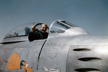 Aldrin in the cockpit of a plane, with the canopy pulled back. Aldrin looks at the camera, smiling, and points his index finger into the sky. He wears a dark flight suit with a patch on the right breast. He has a ring on his pinky finger. A graphic on the side of the plane shows Pluto the dog chasing a Korean MiG.