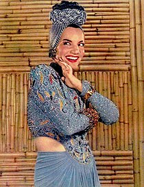 A smiling Carmen Miranda against a bamboo wall