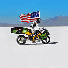 Chip Yates Rides the electric motorcycle at Bonneville carrying an American Flag.