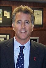 A middle-aged man, wearing a dark blazer, light-coloured shirt, and a blue and white tie.