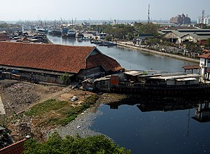 "Penjaringan - The port of Sunda Kelapa. Penjaringan Subdistrict is the area to the left of the port. The right side of the port is the Administrative Village of Ancol in Pademangan Subdistrict. The historic Pasar Ikan (""fish market"") is the building on the foreground, built on a restored warehouse of Dutch East India Company (VOC)."