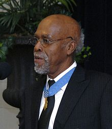 Clarence Sasser, a gray-haired black man standing at a microphone, wearing a medal on a blue ribbon around his neck.