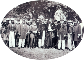 A photograph showing a large group men, most of whom wear uniforms, standing beneath shade trees