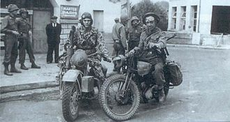 82nd Armored Reconnaissance Battalion - At Pacy-sur-Eure, France, American and British troops meet on August 27, 1944. In camouflage Cpl. Gordon C. Powell on a Harley-Davidson WLA, with the 82nd Armored Reconnaissance Battalion, poses next to British dispatch rider Baltins Dogoughs.