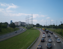 A six lane freeway curving to the right. The opposing directions of travel are separated by a grassy median. Power lines cross the highway, and apartments are visible in the background