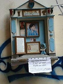 Photographie en couleurs. Autel en bois de couleur bleu ciel commune à l'Argentine et à Naples, accroché dans un mur des rues de Naples.