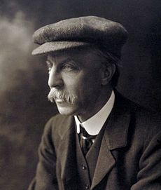 Black and white portrait photograph of Sir Edward Albert Sharpey-Schafer, looking to the left, wearing a flat cap and suit. He was a large moustache.