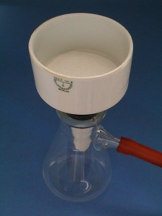 Büchner flask - A Büchner funnel is attached to the flask via a black elastomer adapter. The hose barb is connected via vacuum hose to a vacuum source such as an aspirator. The flask should be clamped before use or the hose will likely cause it to tip.