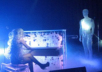 "Poker Face (Lady Gaga song) - Gaga performing the piano version of ""Poker Face"" during The Fame Ball Tour, wearing a dress made of plastic bubbles and playing a transparent piano"