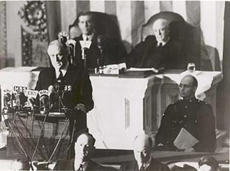 Infamy Speech - Roosevelt delivers the speech to Congress. Behind him are Vice President Henry A. Wallace (left) and Speaker of the House Sam Rayburn. To the right, in uniform in front of Rayburn, is Roosevelt's son James, who escorted his father to the Capitol.