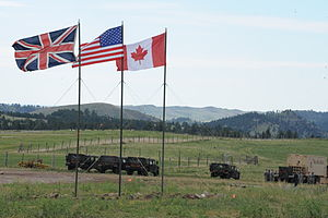 South Dakota National Guard - Flags from the United Kingdom, United States and Canada wave near the entrance to the South Dakota Army National Guard's Golden Coyote training site in Custer State Park in East Custer, S.D.