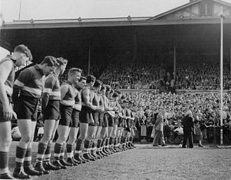 Western Bulldogs - Footscray players line up for the unfurling of the 1954 premiership flag.