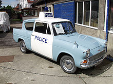 Ford Anglia car in pale blue paint, with white overpainted doors and roof. The roof also carries a Police lightbox sign and flashing blue light.