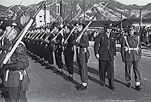 Soldaten in formeller Uniform mit Schlapphuten, blancoed Webgurteln, Strumpfbandern und Schlingen, die wahrend der Parade inspiziert werden
