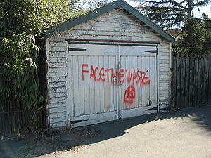 Waste in New Zealand - Graffiti about waste on a garage door in Christchurch (2009).