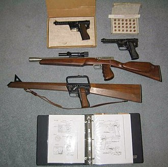 Gyrojet - The Gyrojet Family: two Gyrojet Pistols, a Carbine and the Rifle. In the top-right corner is a box of 13mm Rockets, and at the bottom is a diagram book for the guns.