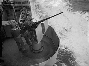 HMS Dido (37) - A 20 mm Oerlikon gunner on board Dido getting a light from a pal between bombing attacks in the eastern Mediterranean, January 1942.