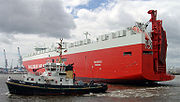 A tugboat shown turning a large RORO cargo ship.