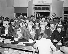 A large crowd of sullen looking workmen at a counter where two women are writing. Some of the workmen are wearing identify photographs of themselves on their hats.