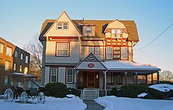 "An intricate three-story beige wooden house with red trim, with snow on the porch roof and the front lawn, with a setting sun lighting the upper stories from the right. It has windows of different shapes and sizes. A front porch is on the right half of the first story, with a triangular projection on the left with a prominent ""36"" in the center. Another triangular section projects from the left hand side of the roof, with a smaller projection with a segmented, more curvilinear roofline to its right. A brick building is visible on the left; in the left front of the yard is an old horse-drawn carriage."