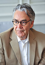 A picture of a man with grey hair. He wears thick-rimmed glasses, a white shirt, and a beige suit.